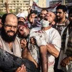Mısır'ın başkenti Kahire'de Adaweya Meydanı'nda sniper ile başında vurulan bir genç ve onu taşıyan iki adam | Fotoğraf: Mosa'ab Elshamy / 27 Temmuz 2013
